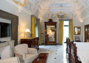 20 Luxury Wedding Venues in Italy Grand Hotel Cocumella classical bedroom with yellow accents and painted ceilings