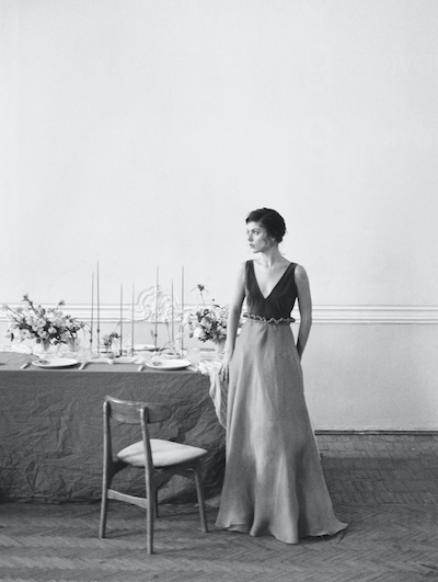 Fine Art Wedding Inspiration black and white photo of the bride standing by the wedding table