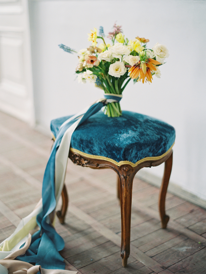 Fine Art Wedding Inspiration with a blue velvet stool with yellow flowers and blue ribbons