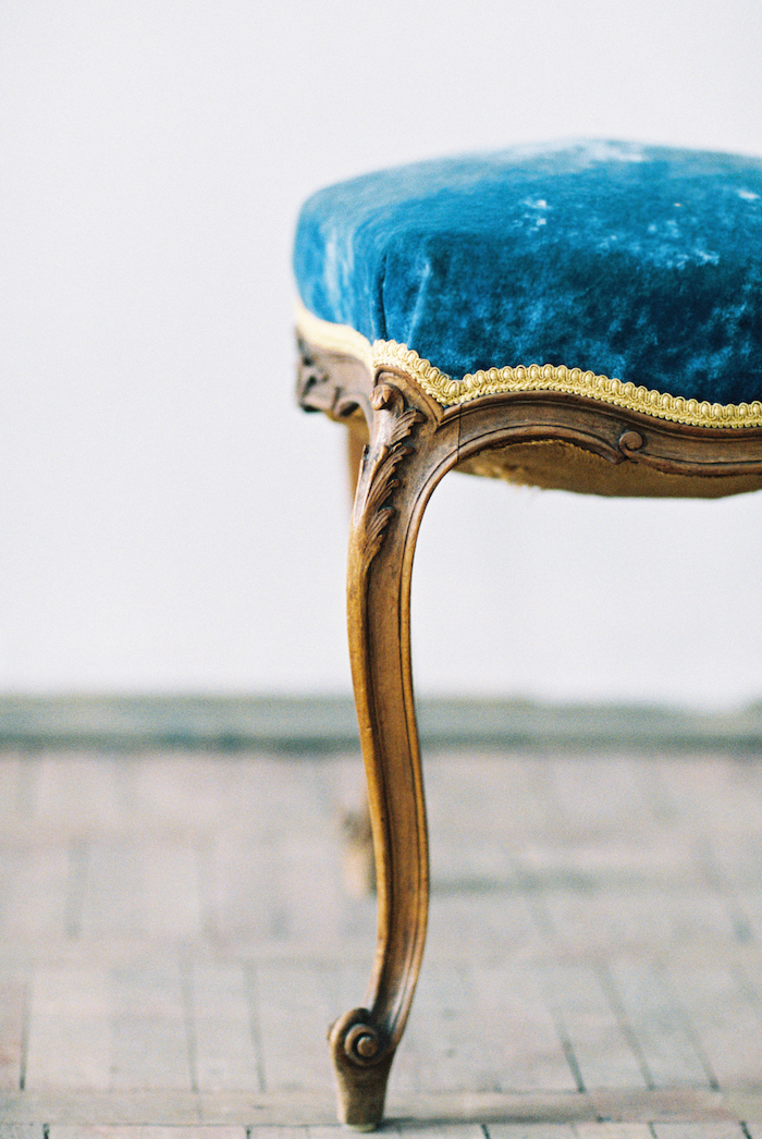 Fine Art Wedding Inspiration with a close up view on the corner of an antique blue velvet stool