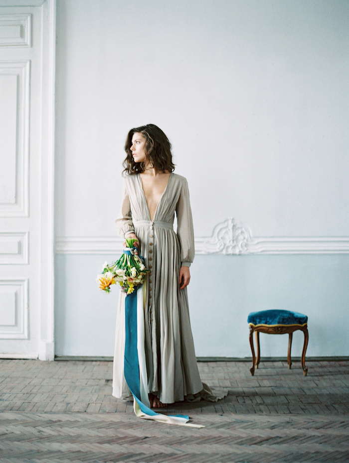 Fine Art Wedding Inspiration with bride in grey dress and holding flowers with a blue velvet stool