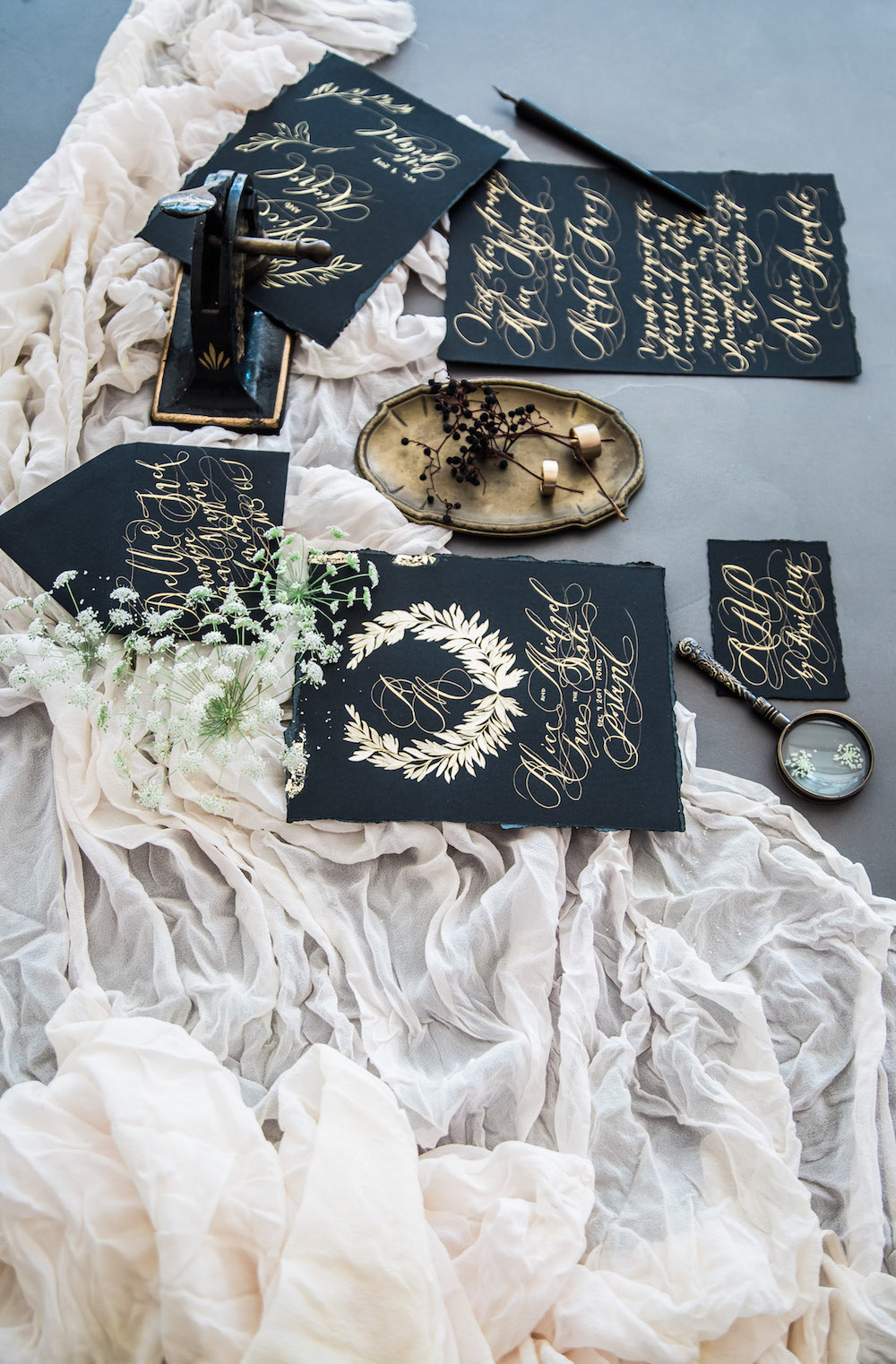 Wedding Invitation Timeline showing a black wedding stationery suite with gold hand painted floral detail