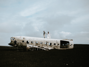 Best Destination Wedding Locations Iceland couple standing on plane wreckage