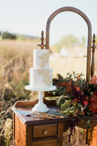 Rich Red & Gold Autumn Wedding cake display on wooden furniture