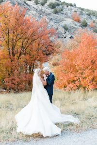 Rich Red & Gold Autumn Wedding couple standing next to orange trees