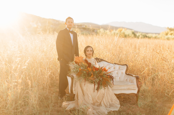 Rich Red & Gold Autumn Wedding couple with bride seated