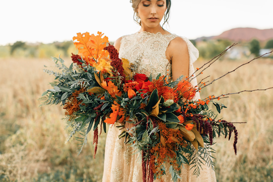 Thankful for Love Autumn inspired style shoot with large red flower bouquet and bride in gold dress