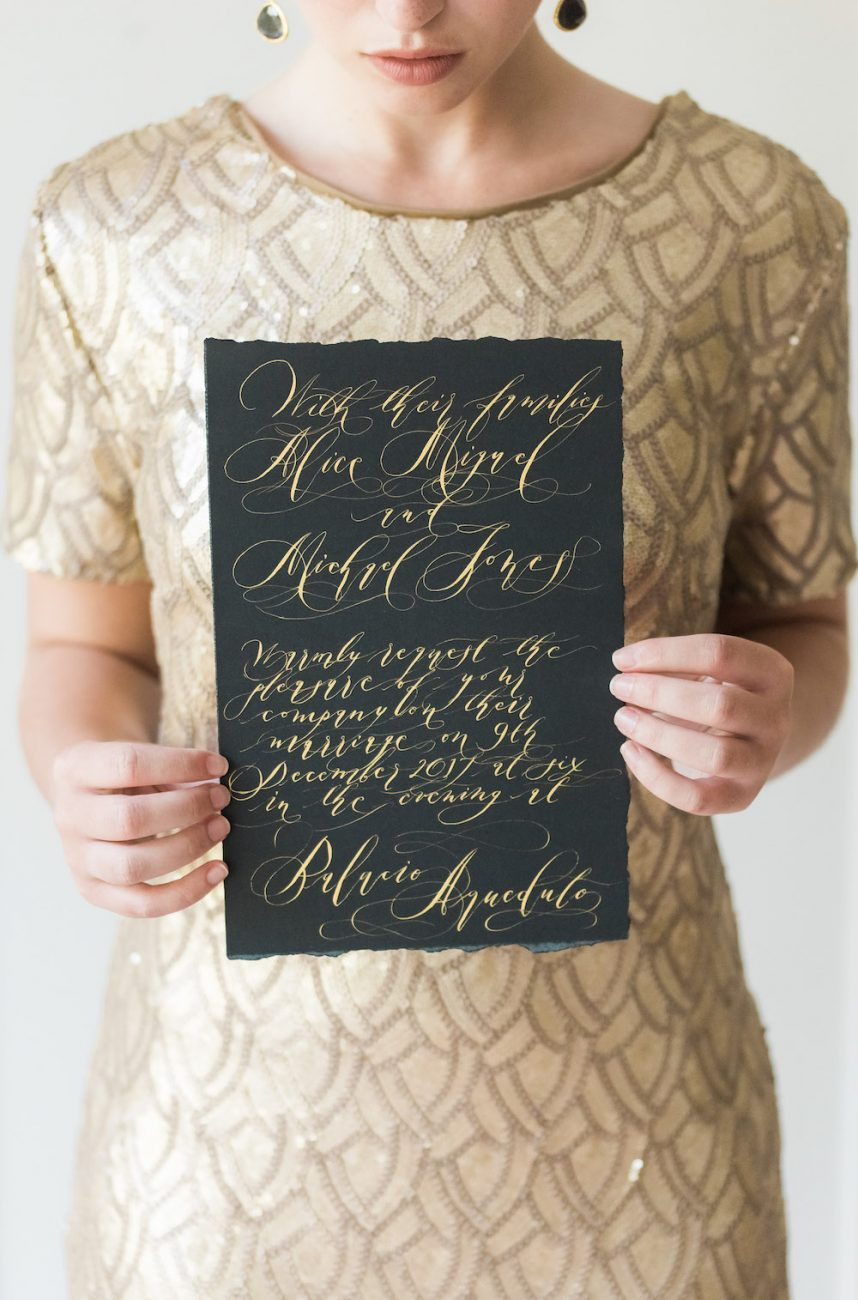 Fine Art Black Tie Wedding Inspiration Shoot bride with gold dress and black invitation
