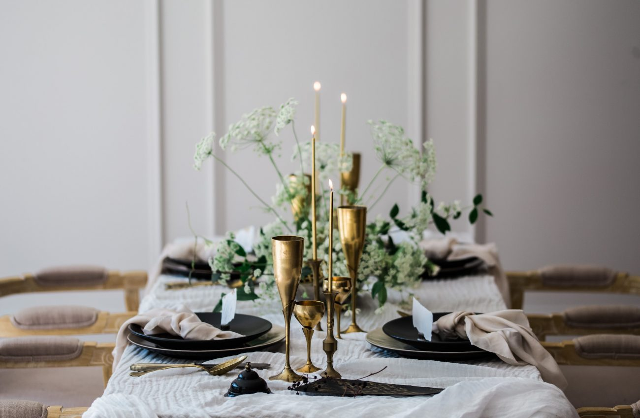 Fine Art Black Tie Wedding Inspiration Shoot with gold lit candles on a table setting