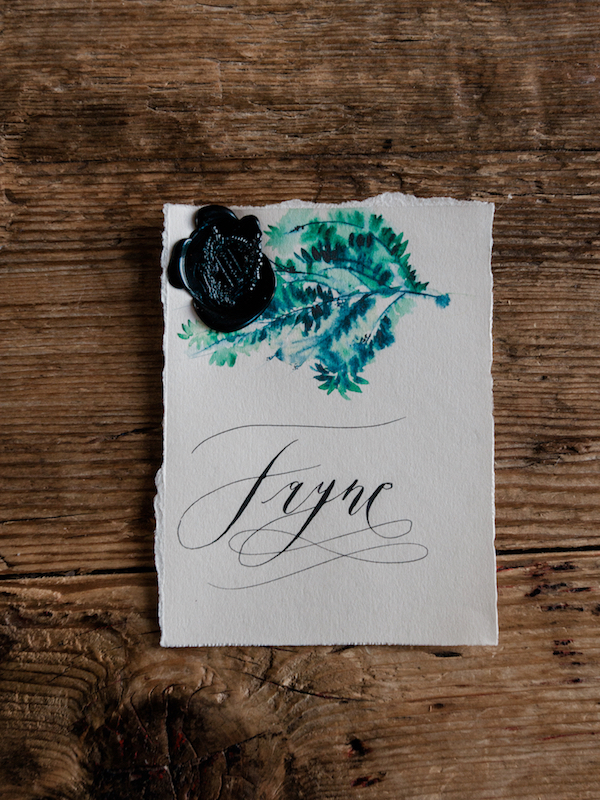 Luxury Handmade Wedding Invitations place name with green leaves and black wax