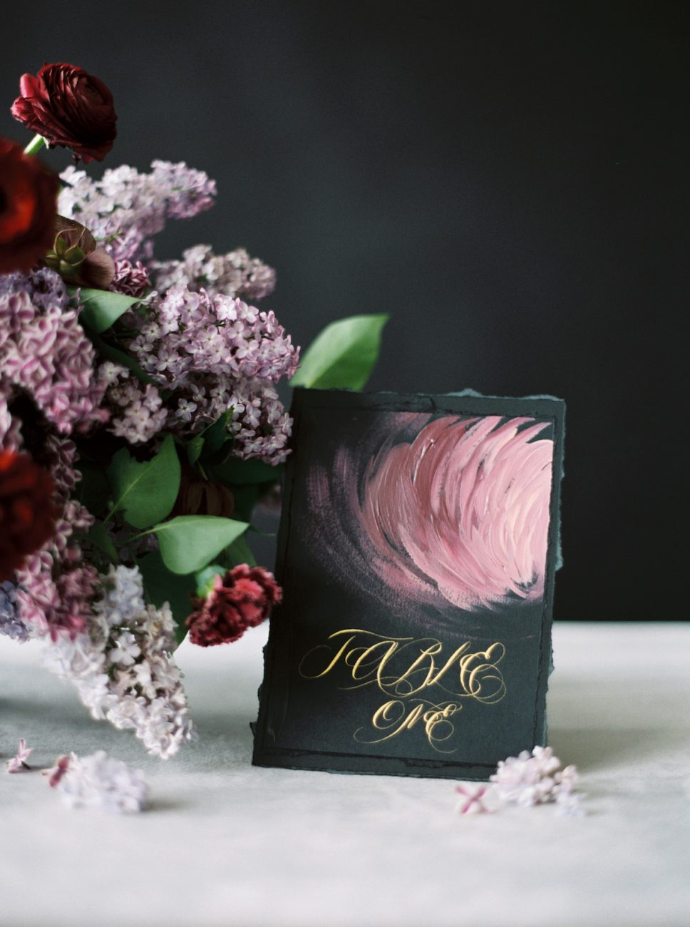 Moody Black Wedding Inspiration black table number with gold calligraphy and deep pink abstract flower