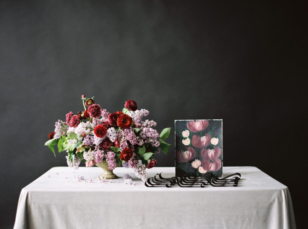 Moody Black Wedding Inspiration escort card table idea with flowers and art display