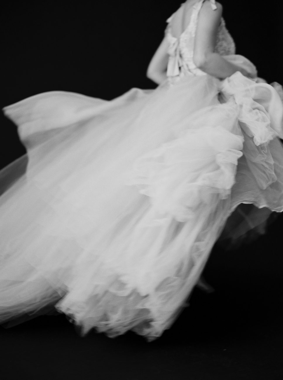 Moody Black Wedding Inspiration with black and white photo showing movement of a gown