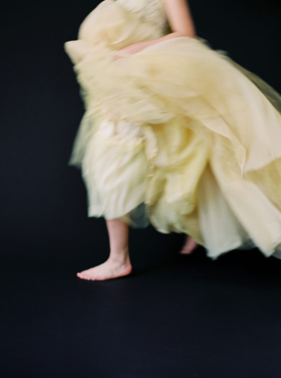 Moody Black Wedding Inspiration with bride in a yellow chiffon bridal gown running
