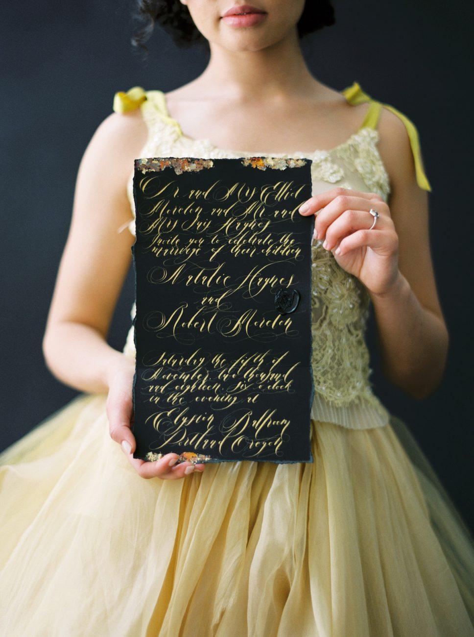 Moody Black Wedding Inspiration_bride holding black wedding invite with gold calligraphy