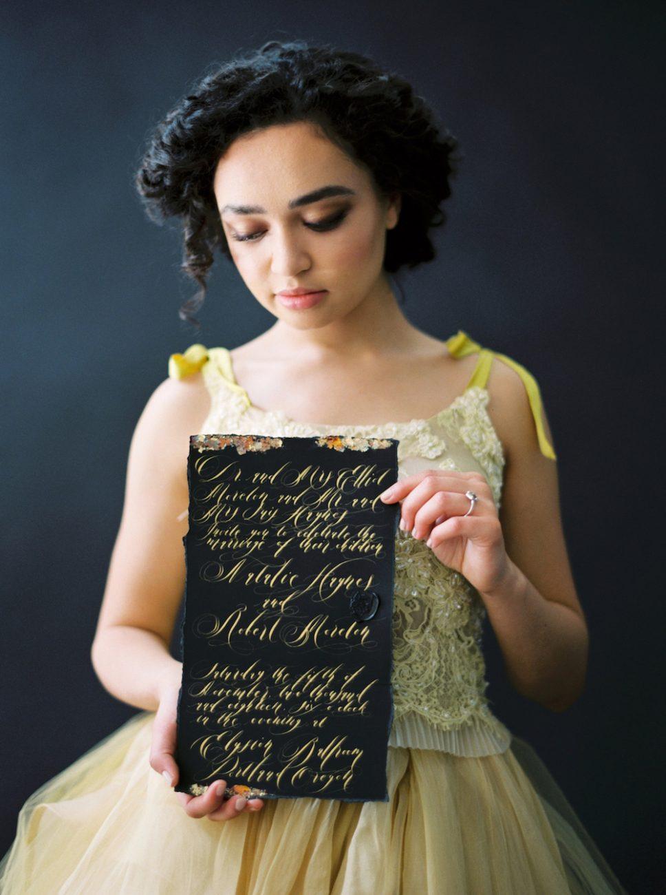 Moody Black Wedding Inspiration_bride holding invitation with bronze foil