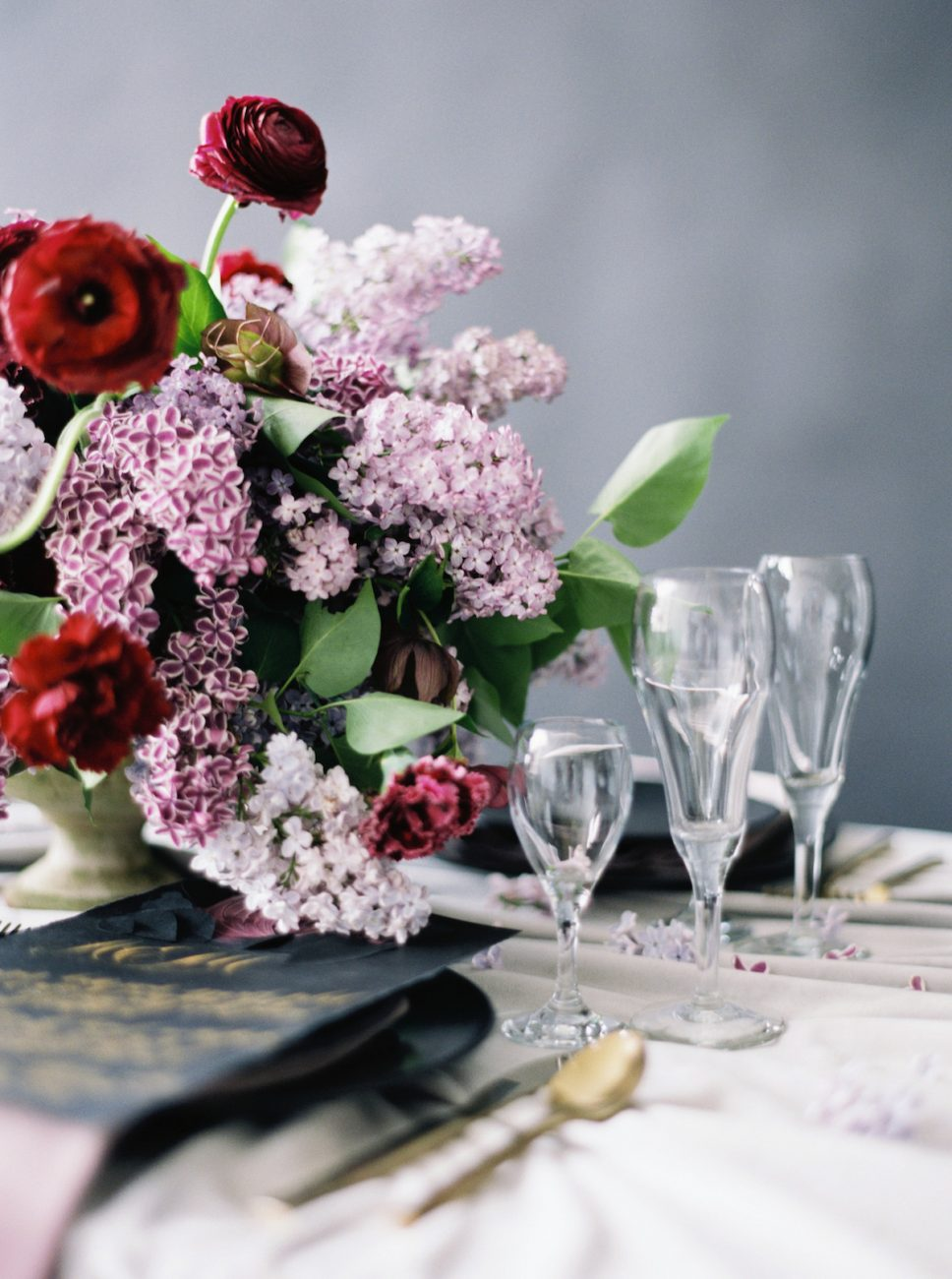 Moody Black Wedding Inspiration_close up on red and pink flowers with clear glasses