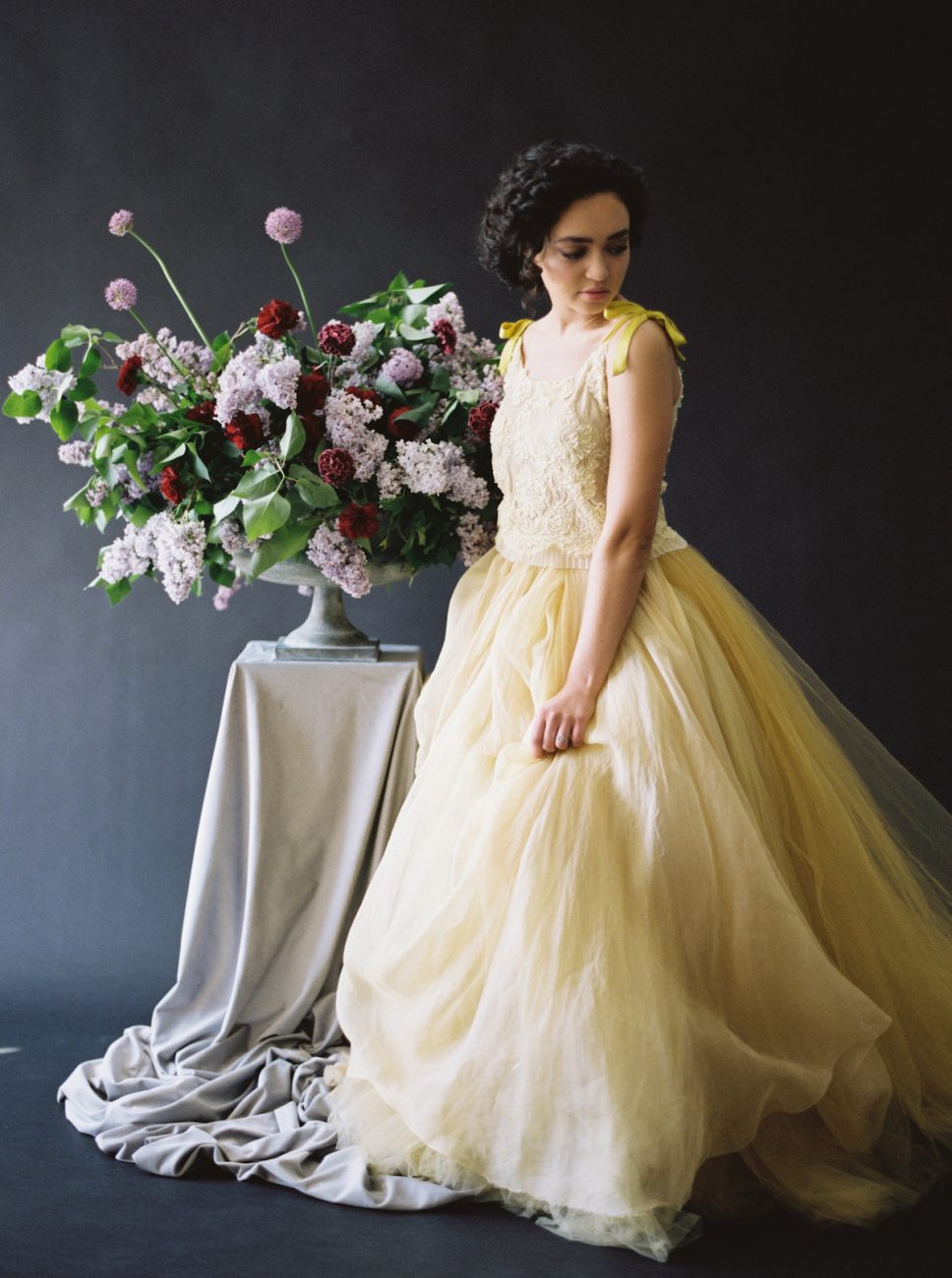 Moody Black Wedding Inspiration_large urn with flowers next to bride in yellow dress