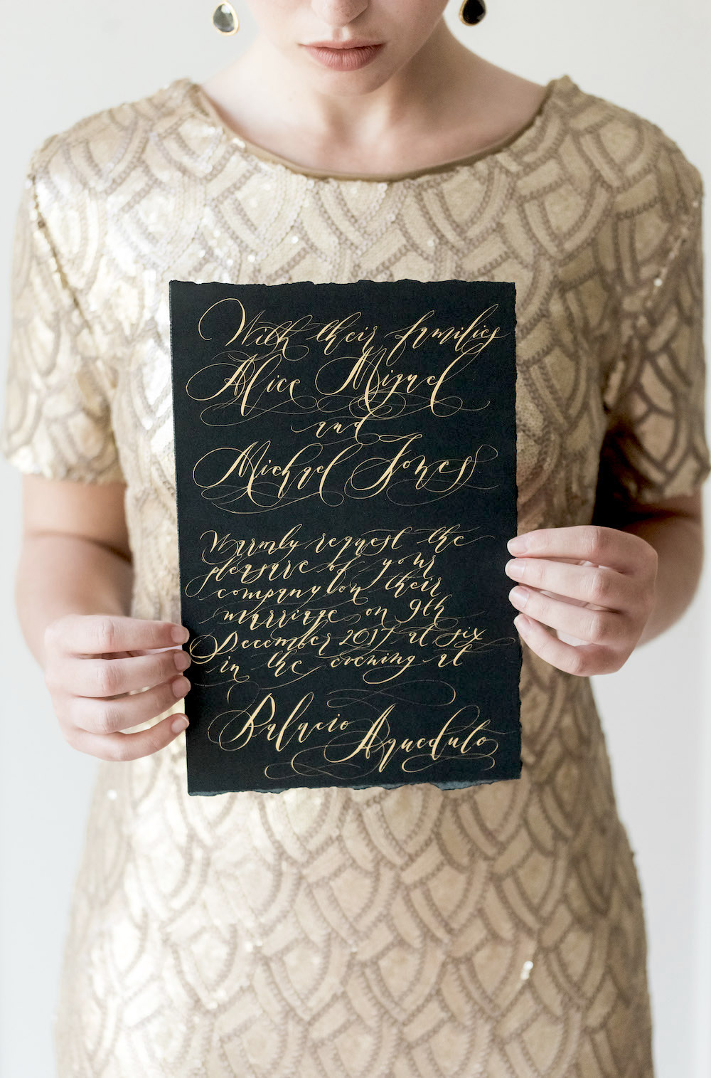 London Wedding Invitations bride in a gold dress holding a long black invite with gold calligraphy
