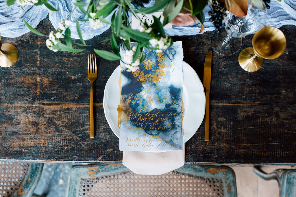 London Wedding Invitations featuring a wedding menu with gold calligraphy and a French bee design displayed on a table