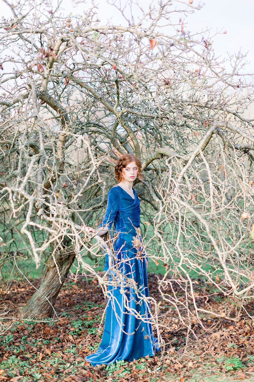 Baroque Wedding bride standing by a tree with blue velvet dress