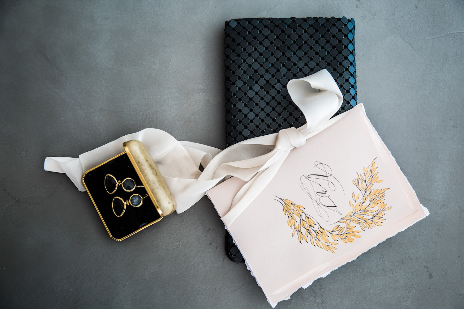 Vow book made on pale blush paper with gold leaves design styled on a black handbag
