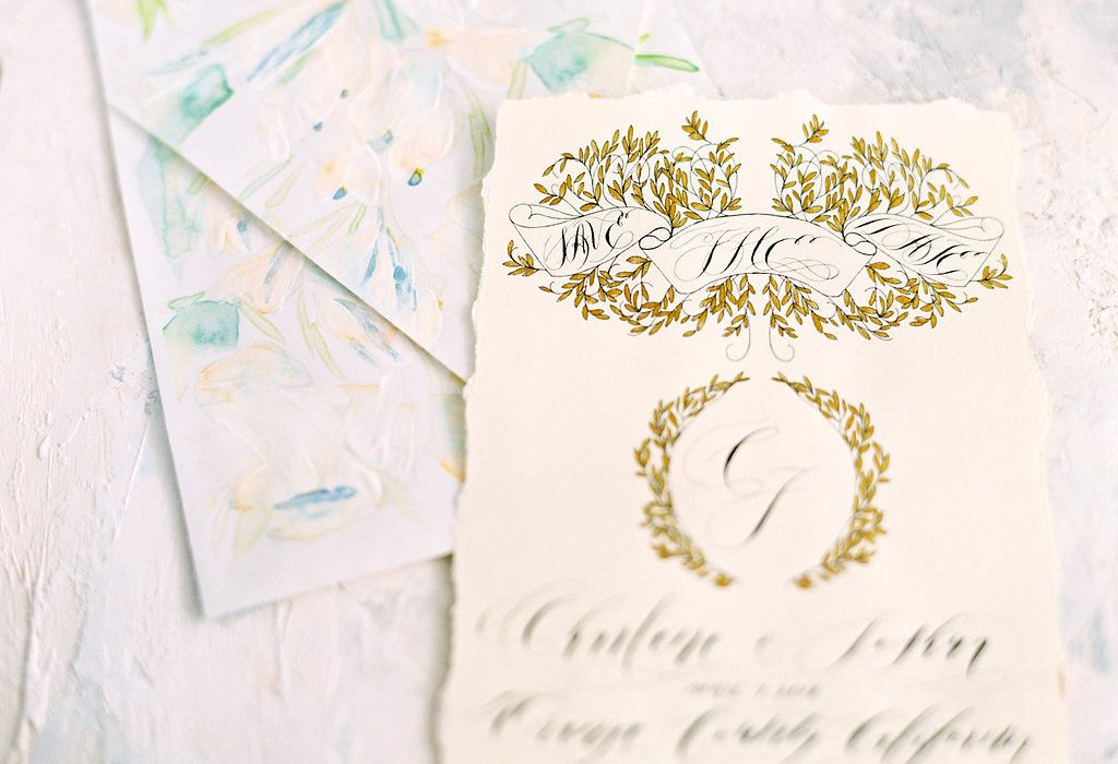 modern wedding invitation wording with a gold crest design