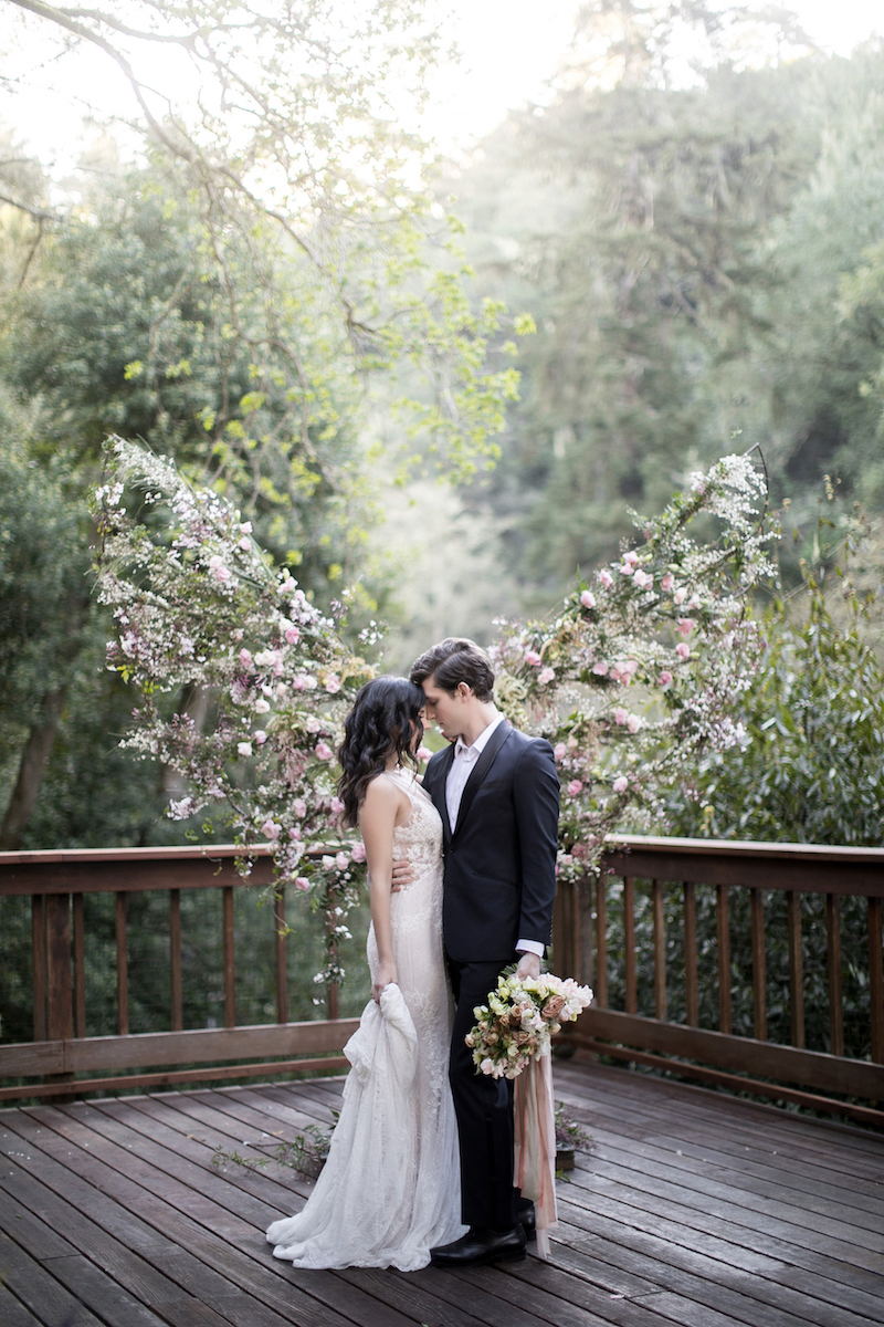 Couple exchanging their wedding vows in front of large floral wings