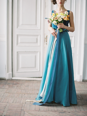 Fine Art Wedding Inspiration bride wearing blue wedding dress and holding bouquet with ribbons