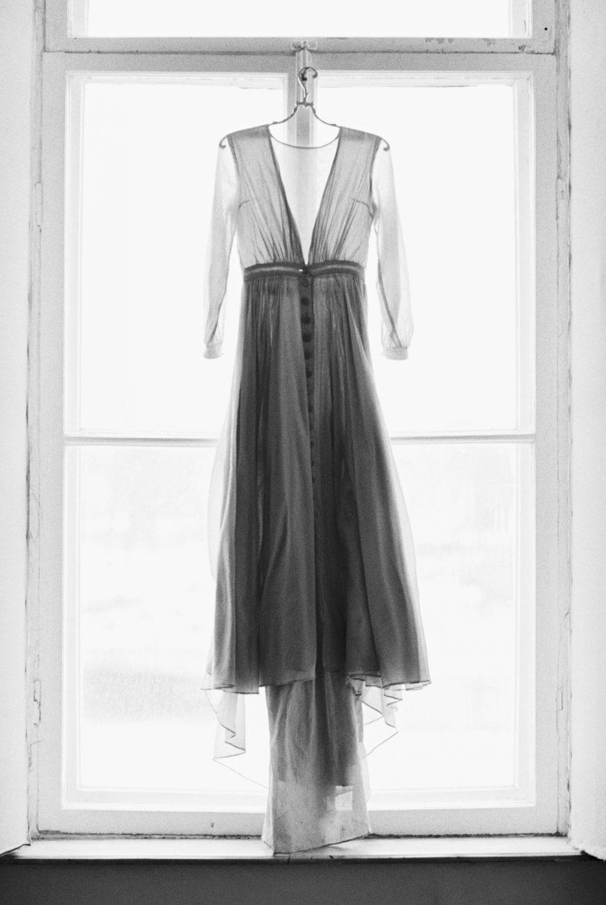 Fine Art Wedding Inspiration with grey custom designed wedding dress hung onto window