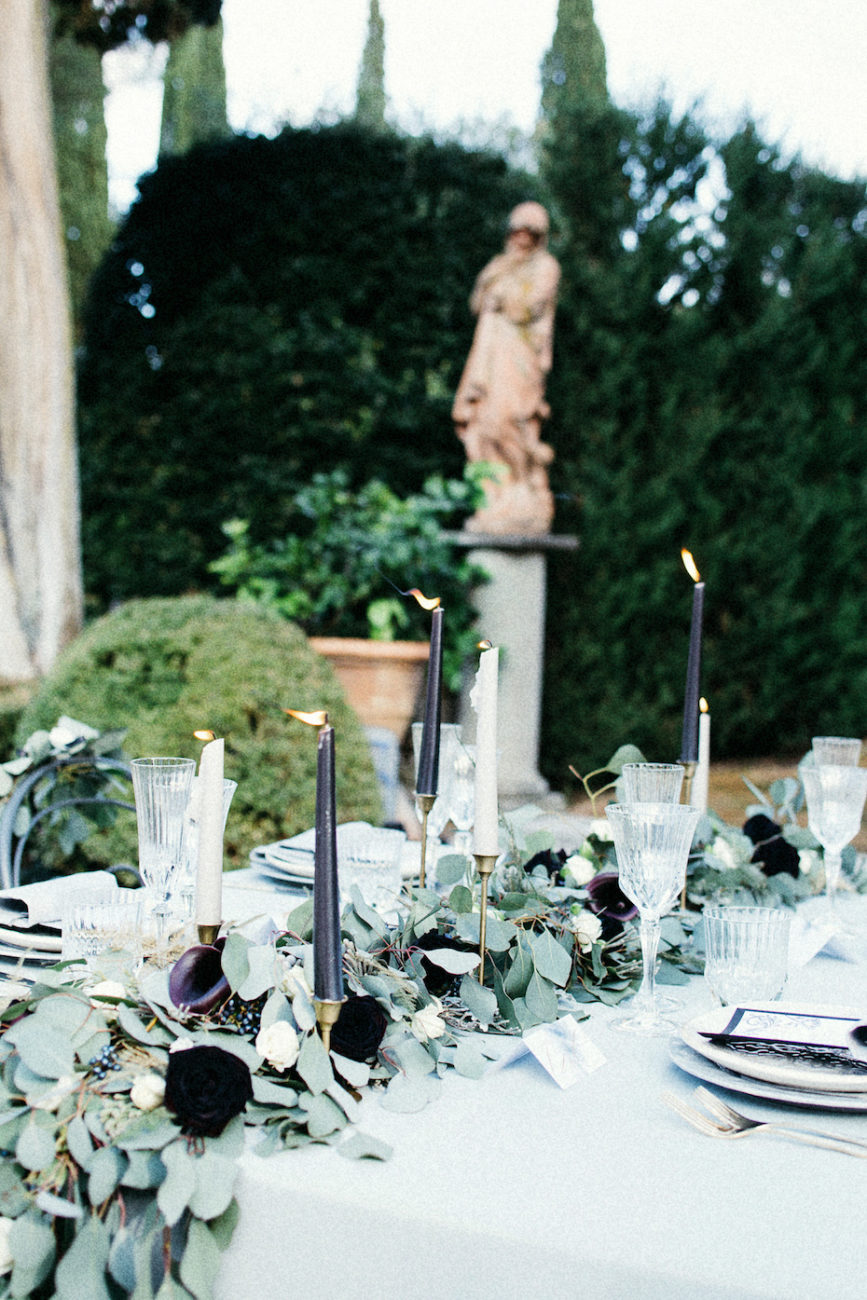 Style Shoot in Tuscany, Italy bridal reception table decoration with leaves, ferns and dark red flowers