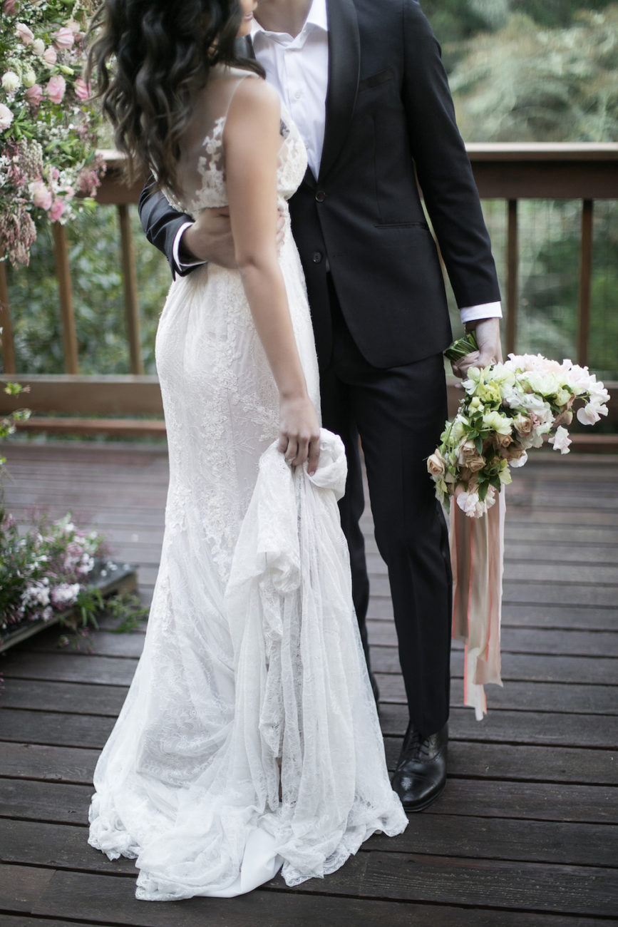 Neutral Wedding Inspiration_groom holding bride's bouquet with ribbons