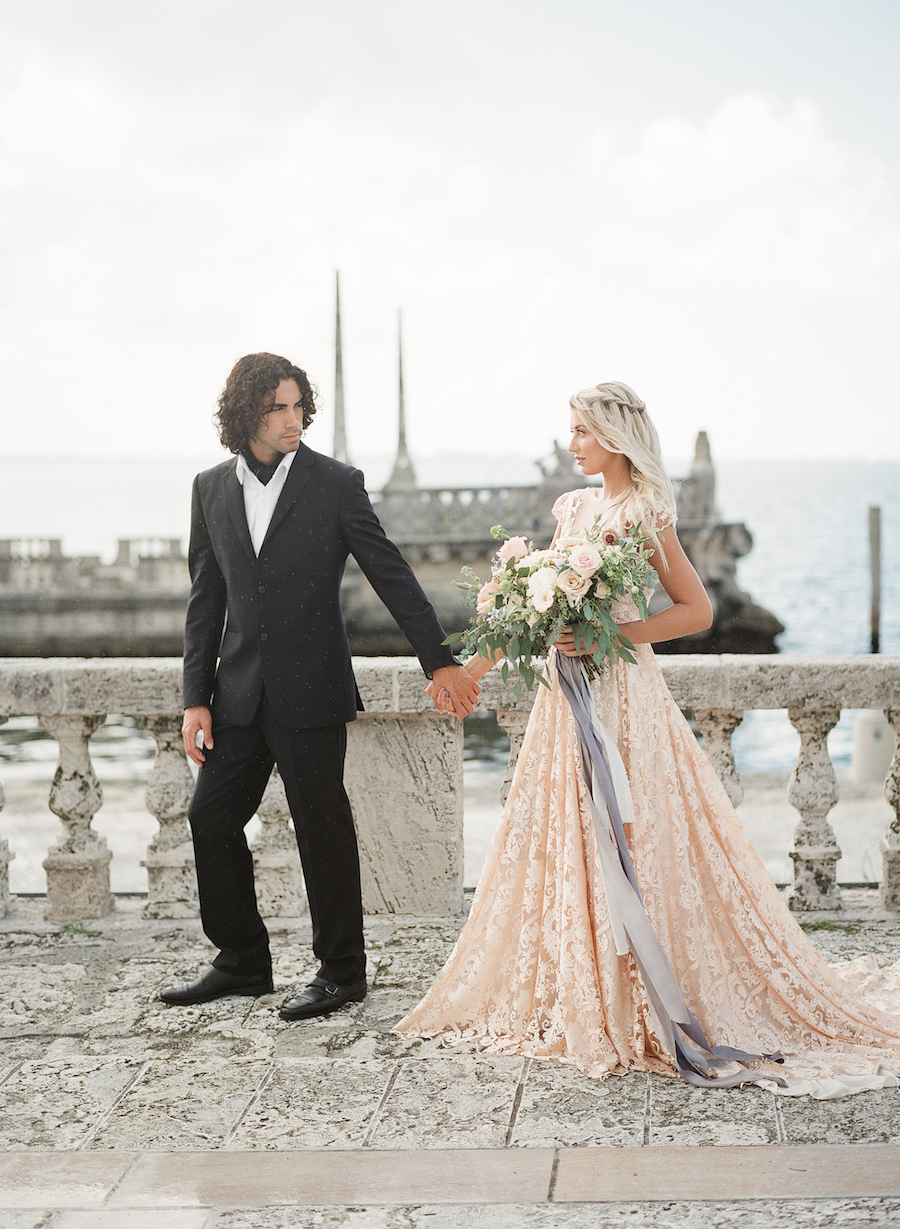Vizcaya Wedding Inspiration Bride holding groom's hand in front of sea