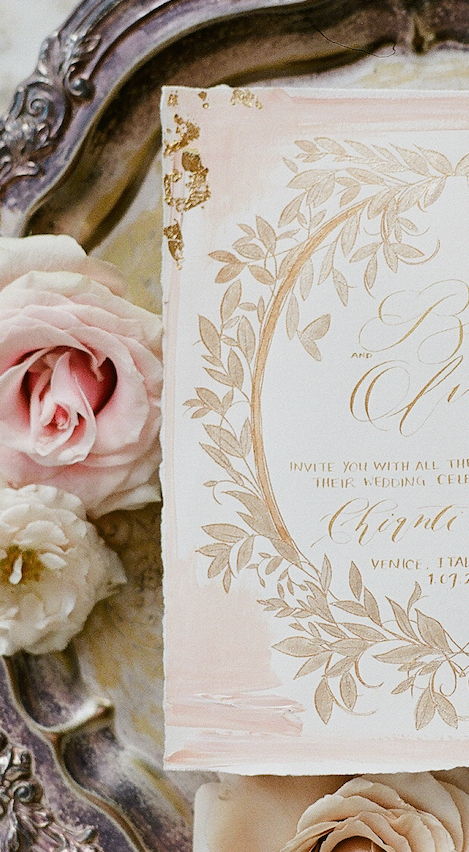 Vizcaya Wedding Inspiration close up view of illustrated wedding invitation with gold leaves and gold calligraphy