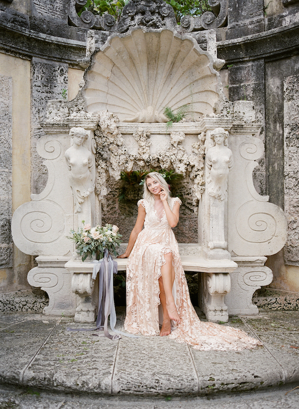 Vizcaya Wedding Inspiration with bride in a blush lace dress sitting in Vizcaya gardens