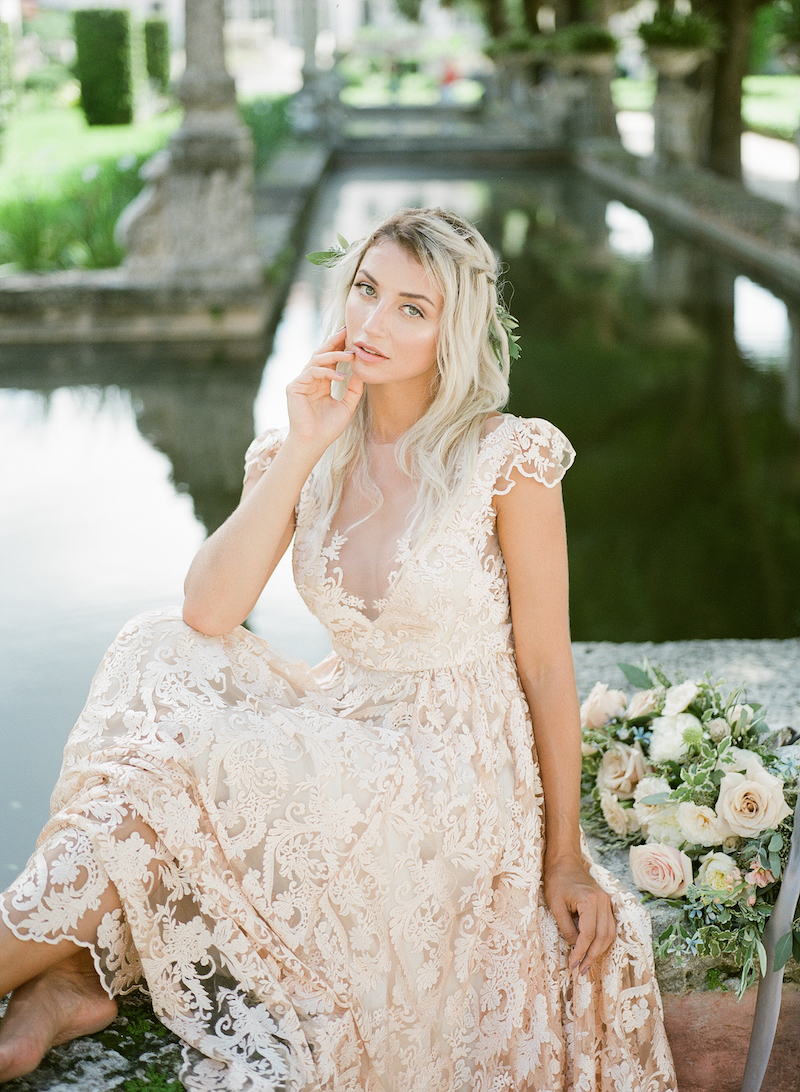 Vizcaya Wedding Inspiration with bride in a pale blush lace dress sitting by the water with her bouquet