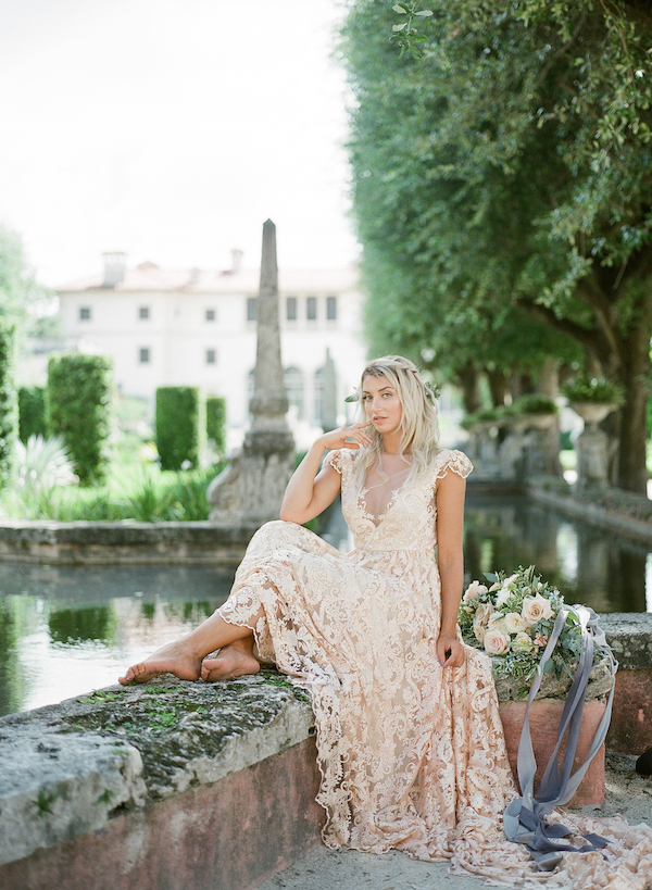 Vizcaya Wedding Inspiration with bride sitting on the water's edge in the Vizcaya gardens