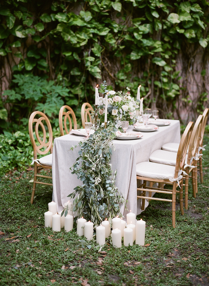 Vizcaya Wedding Inspiration with leaves flowing off table and candles on the grass