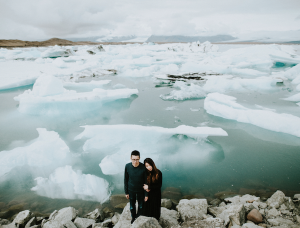 Best Destination Wedding Locations Iceland couple standing next to icebergs and mountains view