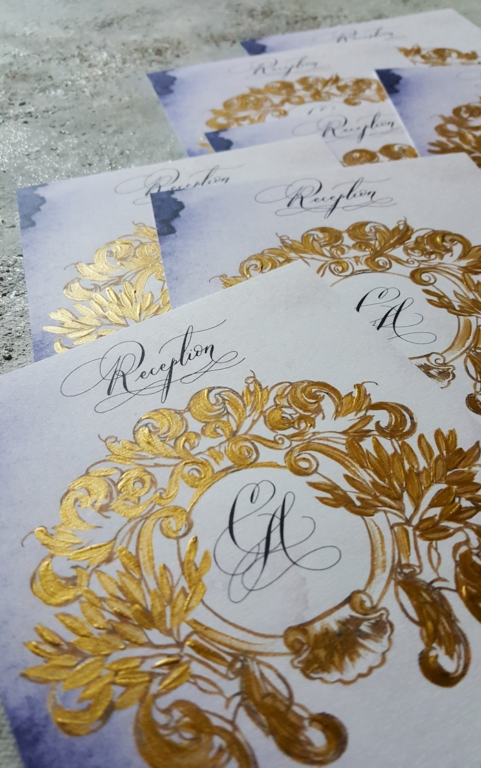 Hand painted wedding invitations with a dark gold crest design