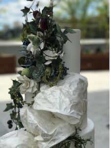 luxury wedding cake designers green florals and white large textured bow