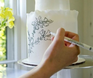 luxury wedding cake designers hand drawing flowers onto a cake