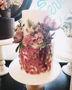 luxury wedding cake designers white cake with little pink blossoms