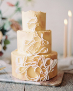 luxury wedding cake designers white ribbon design on creamy yellow icing