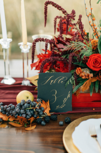 Rich Red & Gold Autumn Wedding table setting with bright red flowers