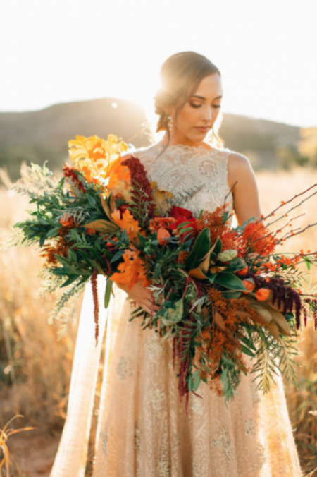 Thankful for Love Autumn inspired style shoot bride holding large bouquet with red flowers