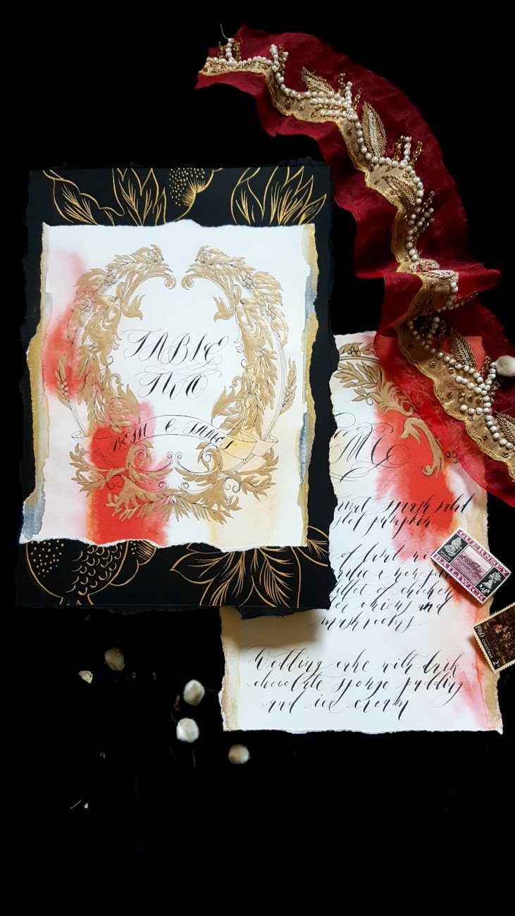 Hand Painted Wedding Stationery table number with orange watercolour and gold painted leaves on black background
