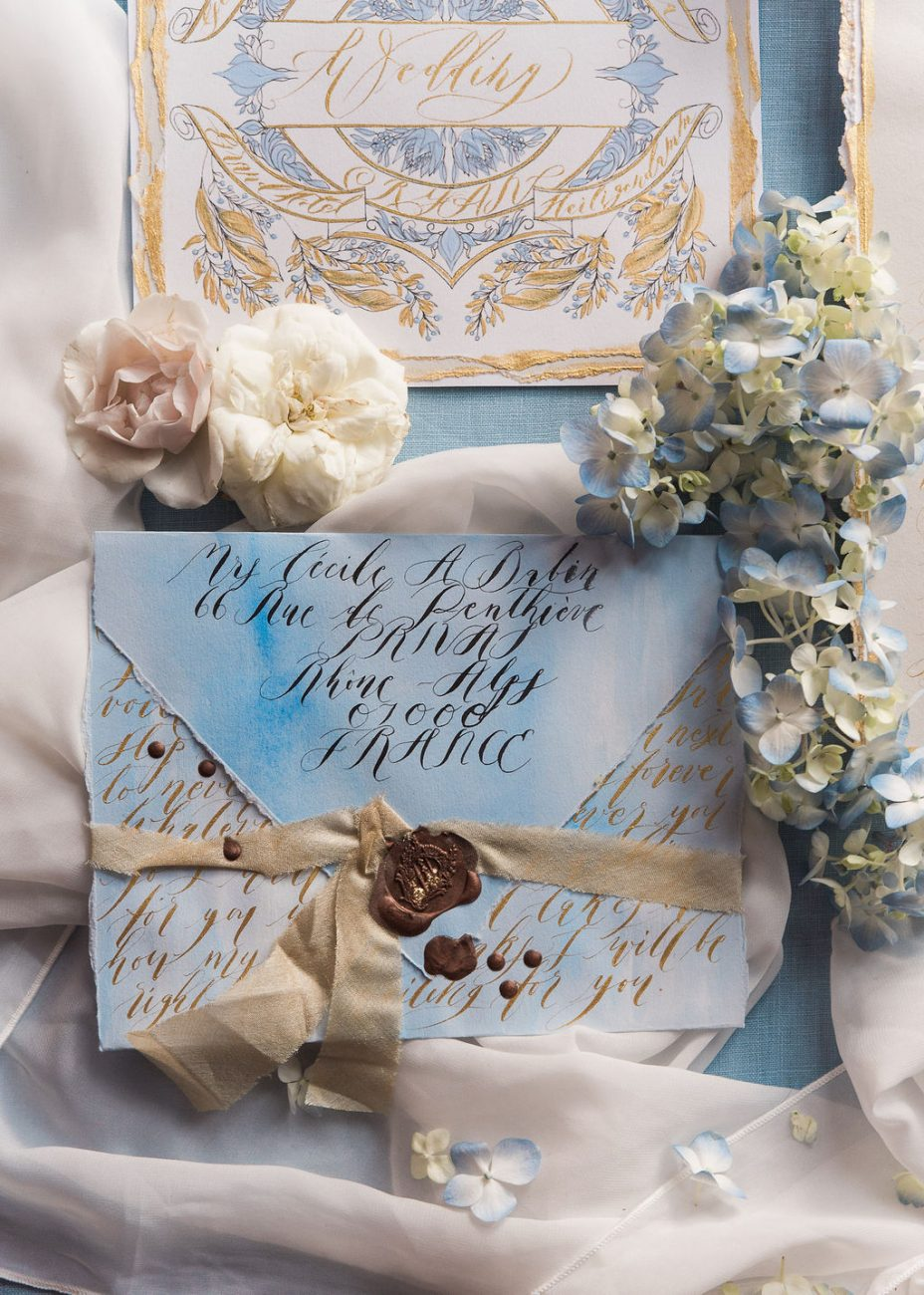 French inspired gentle blue and gold wedding stationery featuring a blue watercolour and gold calligraphy envelope