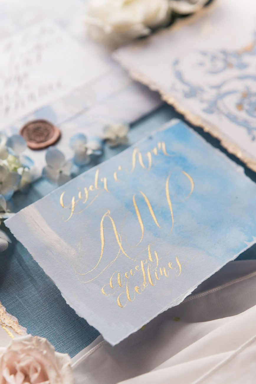 Gold calligraphy rsvp card with blue watercolour accents