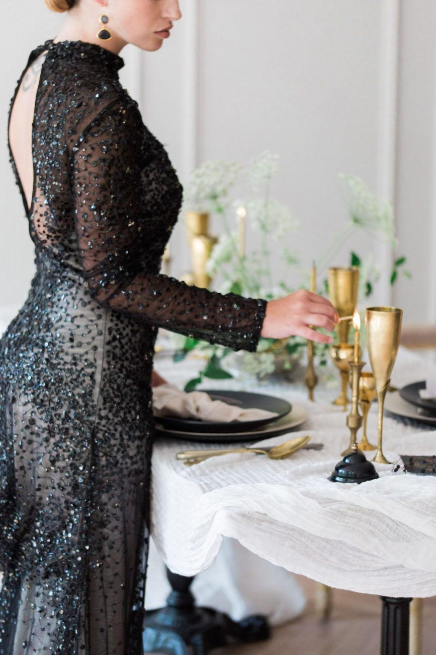 Fine Art Black Tie Wedding Inspiration Shoot bride in a long black dress lighting candles